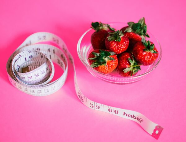 Image of strawberries in a bowl and a rolled up measuring tape with pink background